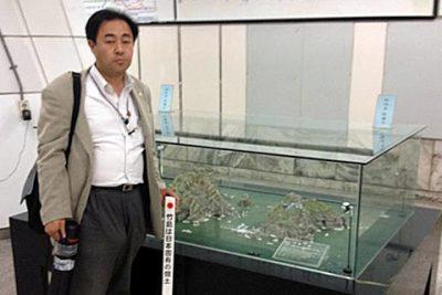 金浦空港駅で大きなショーケースに入った竹島の模型を発見し、その前で「竹島の碑」を袋から取り出して記念撮影。このあと暴漢に襲われる。